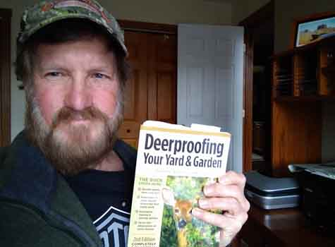 Tony holding how to keep deer out of your garden book